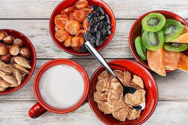Zdrowe śniadanie. płatki z mlekiem, orzechami i suszonymi owocami.