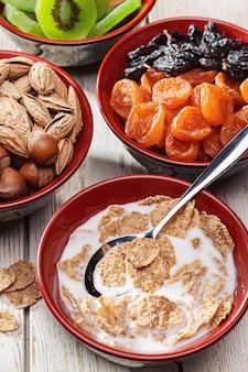 Zdrowe śniadanie. różnorodność jedzenia na białym drewnianym stole w kuchni. płatki zbożowe z mlekiem, bakaliami i orzechami.