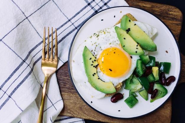 Zdrowe śniadanie składające się z tostów z awokado, pieczywa pełnoziarnistego i jajka sadzonego oraz sałatki burrito na białym talerzu. widok z góry