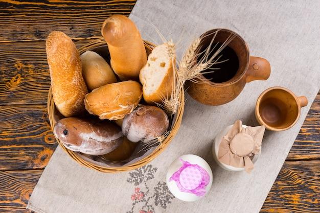 Zdrowe śniadanie składające się ze świeżo upieczonego chrupiącego pieczywa dla smakoszy i mleka serwowane w butelkach, widok z góry