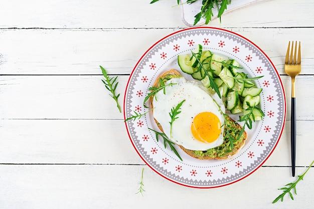 Zdrowe śniadanie. świąteczny brunch. kanapka z awokado z jajkiem sadzonym i świeżą sałatą ogórkową z rukolą na zdrowe śniadanie lub przekąskę. widok z góry, miejsce na kopię