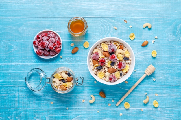 Zdrowe śniadanie. świeża muesli, musli z orzechami i mrożonymi jagodami. widok z góry. skopiuj miejsce