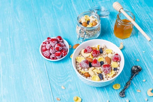 Zdrowe śniadanie. świeża muesli, musli z orzechami i mrożonymi jagodami