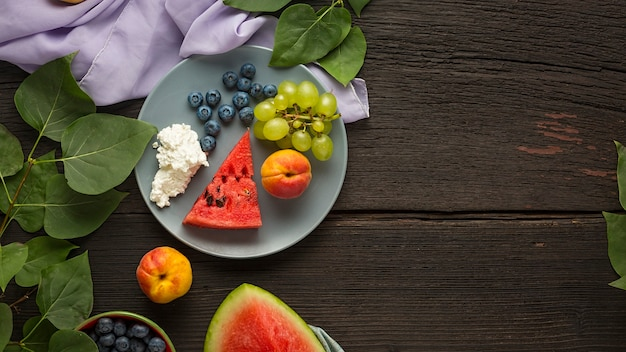 Zdrowe śniadanie. świeże, soczyste owoce i twarożek w talerzach na drewnianym stole z miejsca na kopię