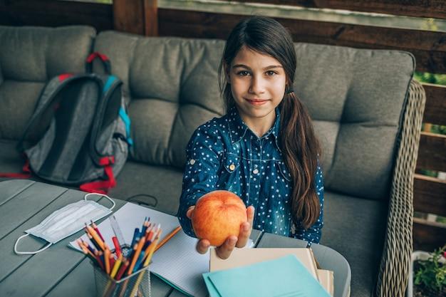 Zdrowe śniadanie szkolne, brzoskwinia w rękach uczennicy. przekąska podczas pracy domowej