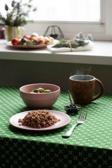 Zdrowe śniadanie. talerz gryki, sałatki, miska dżemu i herbaty.