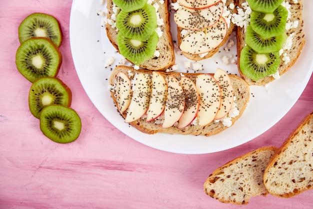 Zdrowe śniadanie tosty z kiwi, jabłkiem, twarogiem i nasionami chia