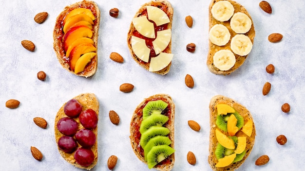 Zdrowe śniadanie tosty z masłem orzechowym, dżemem truskawkowym, owocami