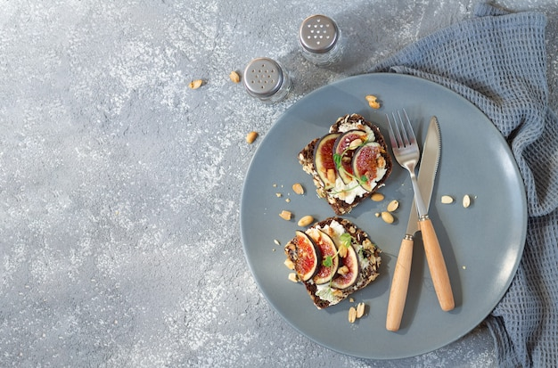 Zdrowe śniadanie tosty ze świeżymi figami, twarogiem, orzechami i przyprawami na talerzu widok z góry