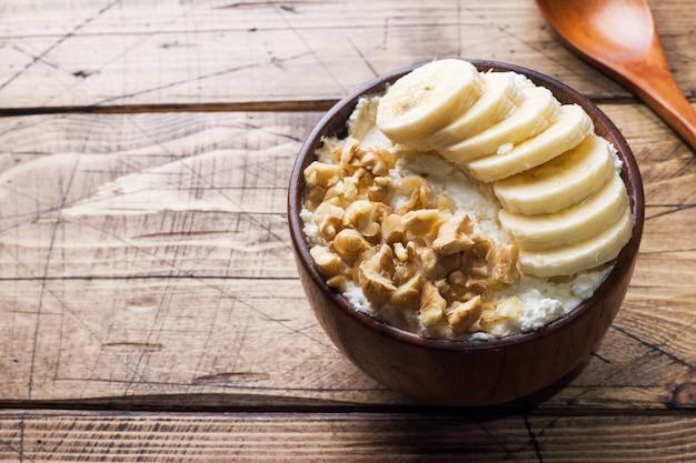 Zdrowe śniadanie. twaróg z bananem i orzechami włoskimi na drewnianym tle.