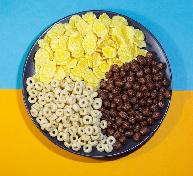Zdrowe śniadanie w formie płatków kukurydzianych i czekoladowych kulek w czarnym talerzu na kolorowym tle