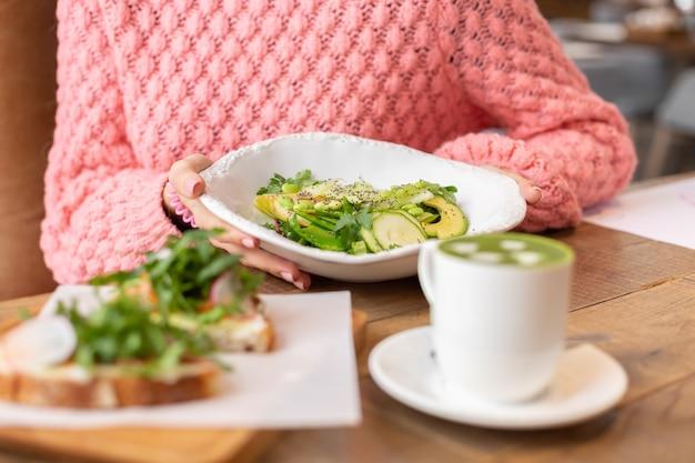 Zdrowe śniadanie w restauracji. zielona sałata, bruschetta z rukolą i łososiem oraz matcha latte