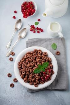 Zdrowe śniadanie z czekoladowymi krążkami kukurydzianymi, jagodami czerwonej porzeczki, jogurtem i herbatą na szarej betonowej powierzchni