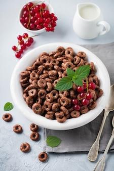 Zdrowe śniadanie z czekoladowymi krążkami kukurydzy, jagodami czerwonej porzeczki, jogurtem i herbatą na szarym betonowym tle