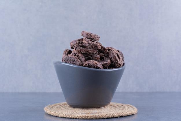 Zdrowe śniadanie z czekoladowymi krążkami kukurydzy w czarnej misce na kamieniu.