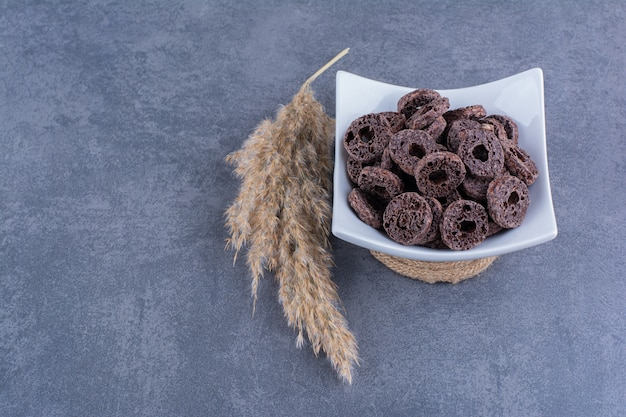 Zdrowe śniadanie z czekoladowymi krążkami kukurydzy w talerzu na kamieniu.