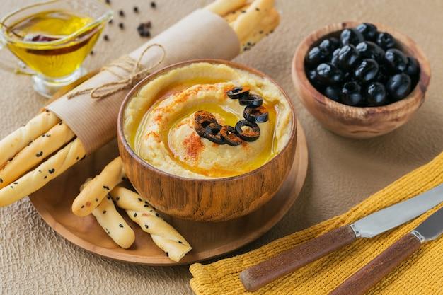Zdrowe śniadanie z domowym hummusem, czarnymi oliwkami i pieczywem chrupkim. dieta i zdrowe przekąski.