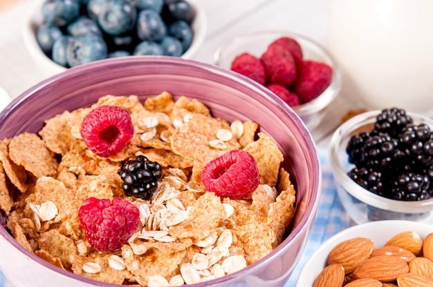 Zdrowe śniadanie z jagodami, mlekiem i migdałowymi płatkami kukurydzianymi na drewnianym stole