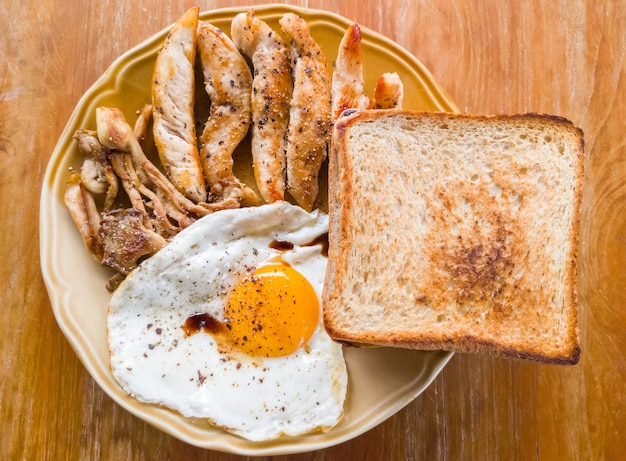 Zdrowe śniadanie z jajkiem sadzonym, grillowaną polędwiczką z kurczaka, grillowanym grzybem i grzanką, na drewnianym stole w lokalnej restauracji, widok z góry na miejsce kopiowania.