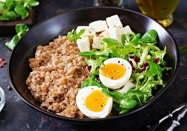 Zdrowe śniadanie z jajkiem, serem, sałatą i kaszą gryczaną w ciemności