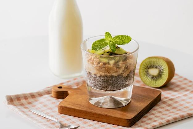 Zdrowe śniadanie z jogurtem, orzechami, kiwi i nasionami chia. miska świeżych owoców.