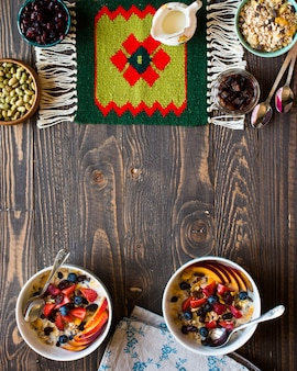 Zdrowe śniadanie z milkmuesli i owocami na drewnianym tle.