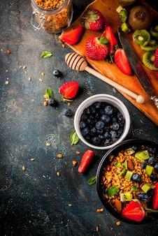 Zdrowe śniadanie z musli lub muesli z orzechami i świeżymi jagodami i owocami - truskawka, jagoda, kiwi, na granatowym stole, widok z góry