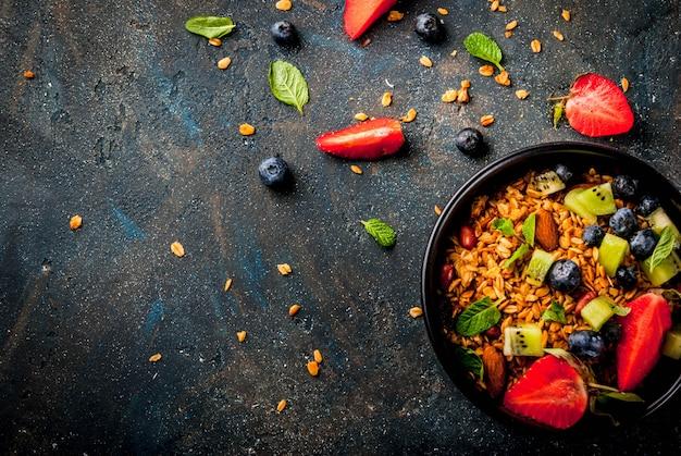 Zdrowe śniadanie z musli lub muesli z orzechami i świeżymi jagodami i owocami