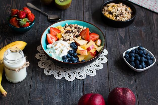 Zdrowe śniadanie z owocami i płatkami na rustykalnym drewnianym
