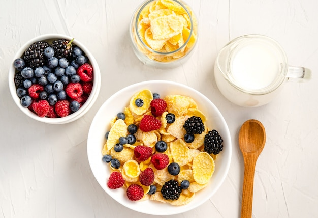 Zdrowe śniadanie z płatkami kukurydzianymi, malinami, jeżynami, jagodami, mlekiem i kawą na białej powierzchni