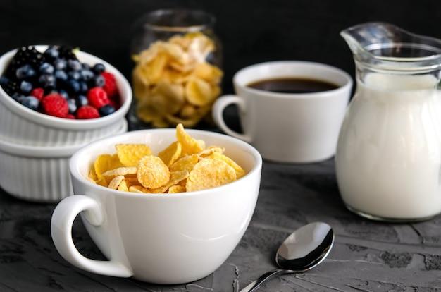 Zdrowe śniadanie z płatkami kukurydzianymi w białej filiżance, jagodami, mlekiem i kawą