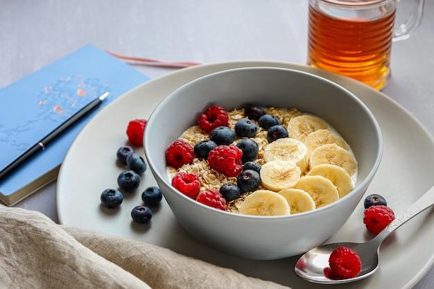 Zdrowe śniadanie z płatkami owsianymi w misce, plasterkami banana, malinami, jagodami, filiżanką herbaty i notatnikiem z długopisem na jasnoszarym blacie