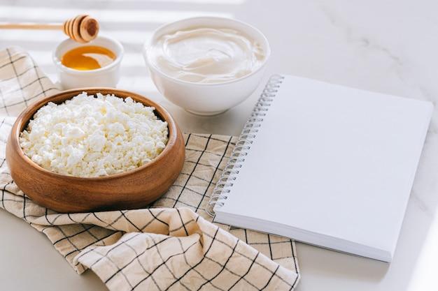 Zdrowe śniadanie z twarogu z kwaśną śmietaną i miodem, czyste puste miejsce na tekst, plan diety na marmurowym stole