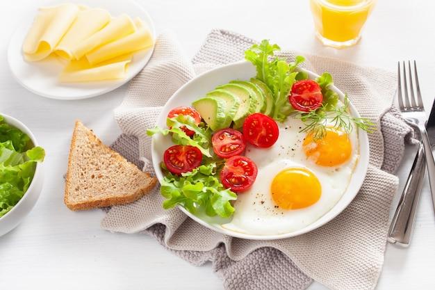 Zdrowe śniadanie ze smażonymi jajkami, awokado, pomidorem, tostami i kawą