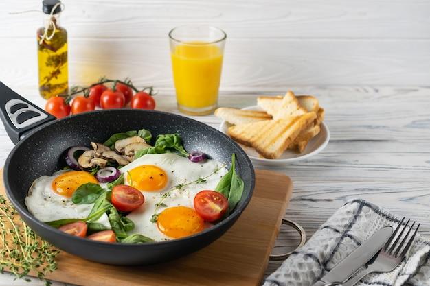 Zdrowe śniadanie ze smażonymi jajkami, pomidorami, pieczarkami i liśćmi szpinaku