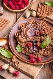 Zdrowe śniadanie ze świeżymi gorącymi goframi serca, naleśniki z kremem czekoladowym i malinami