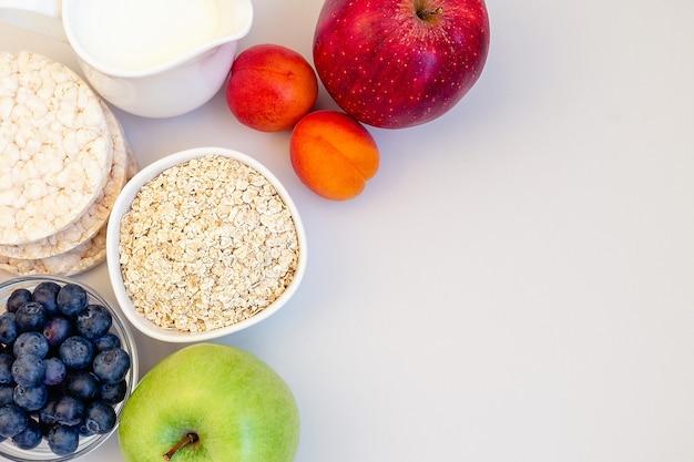 Zdrowe śniadanie ze świeżymi owocami, jagodami, pieczywem chrupkim i mlekiem.