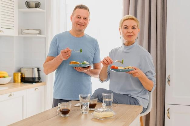 Zdrowe starsze pary pozowanie na kamery jedząc razem zdrowe śniadanie na środku kuchni