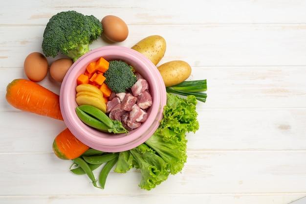 Zdrowe, świeże składniki karmy dla zwierząt domowych na białej powierzchni drewnianych