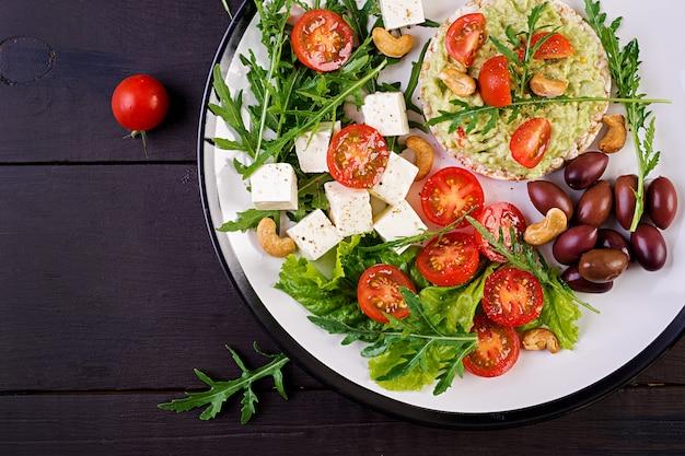 Zdrowe tosty z awokado na śniadanie, guacamole, oliwki kalamata, pomidory, orzechy nerkowca i ser feta
