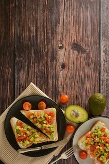 Zdrowe tosty z awokado, pomidorkami cherry i serem na talerzu. drewniany stół.