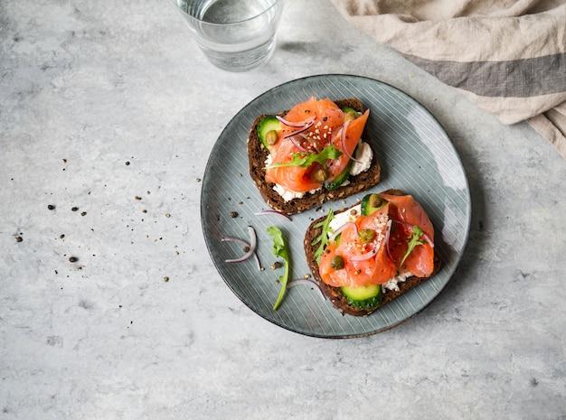 Zdrowe tosty z chlebem żytnim z twarogiem, łososiem, świeżym ogórkiem, kaparami, sezamem, czarnym pieprzem i rukolą na talerzu.