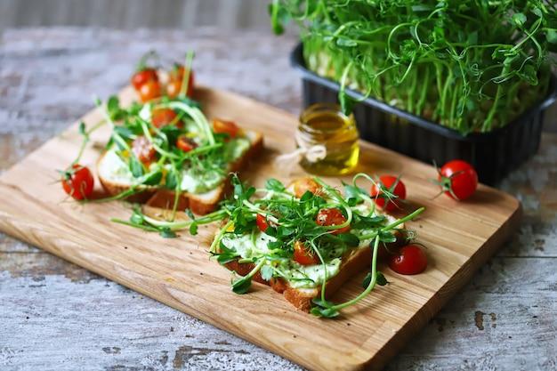 Zdrowe tosty z makaronem awokado, pomidorami koktajlowymi i mikrogreenami.