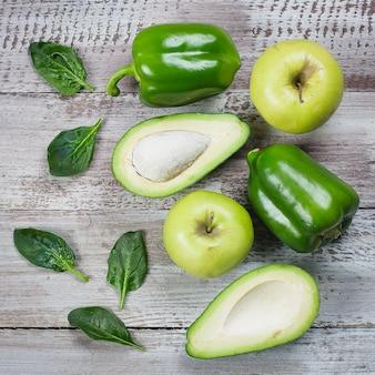 Zdrowe wegańskie jedzenie. kolekcja świezi zieleni warzywa i owoc na drewnianym tle