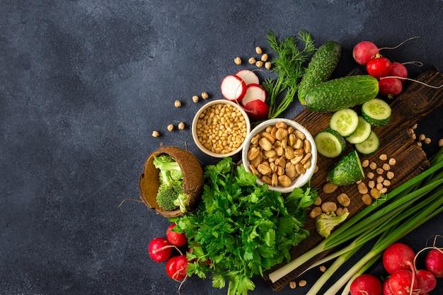 Zdrowe wegańskie jedzenie koncepcja gotowania wegetariańskie. drewniana deska do krojenia kuchnia ze świeżych zielonych warzyw, ziół i zbóż widok z góry