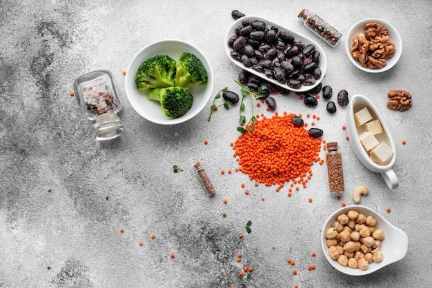 Zdrowe wegańskie jedzenie na betonowym tle z miejsca na kopię. orzechy, fasola, warzywa i nasiona