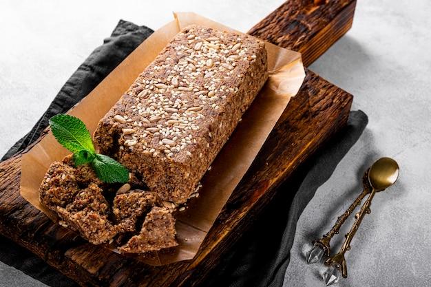 Zdrowe wegańskie słodycze, bezcukrowe orzechy chałwa z nasionami i sezamem na drewnianej desce do krojenia z bliska.