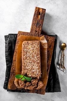 Zdrowe wegańskie słodycze chałwa bezcukrowa z nasionami i sezamem na drewnianej desce do krojenia widok z góry