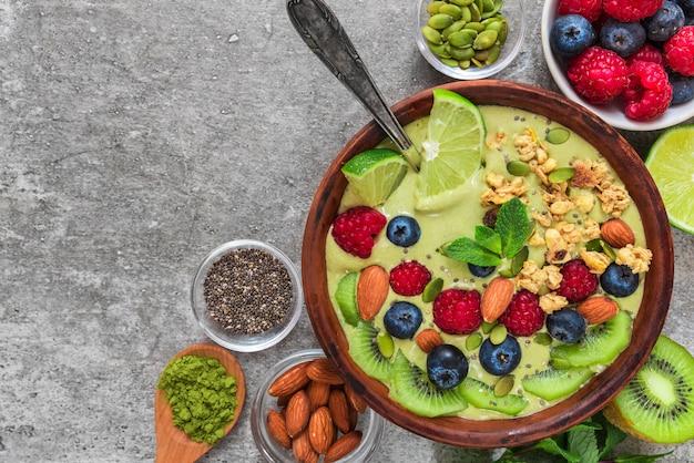 Zdrowe wegańskie śniadanie. matcha herbata miska koktajl z owocami, jagodami, orzechami, muesli i nasionami z łyżką. widok z góry