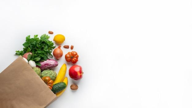 Zdrowe wegańskie wegetariańskie jedzenie w papierowej torebce warzyw i owoców na białym. zakupy w supermarkecie spożywczym i koncepcja czystego wegańskiego jedzenia.